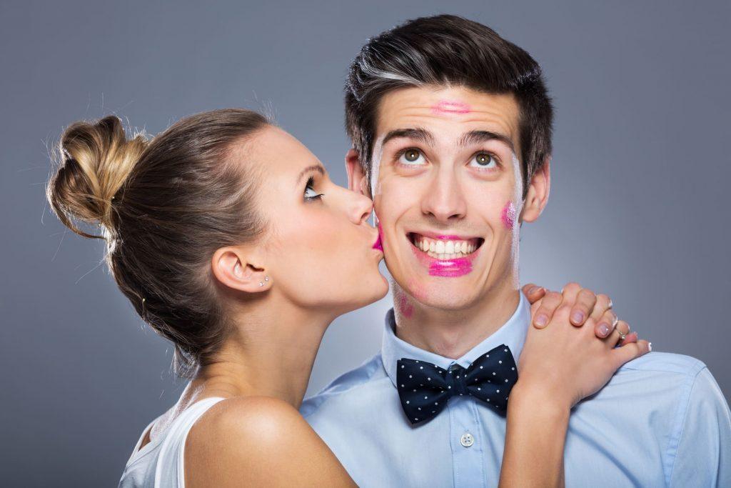 女性が男性のほっぺにキスをしている画像